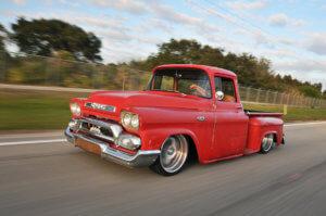 Custom red 1958 GMC 100 running on the highway