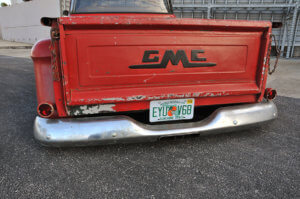 Scratched paint on the rear exterior and dinged chrome bumpers of the custom 1958 GMC 100.