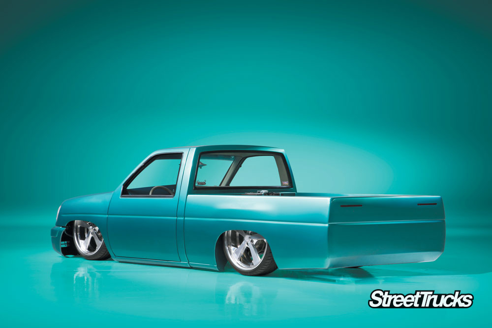 1990s lowered Nissan hardbody truck painted turquoise blue with a Chevy motor against a turquoise blue background